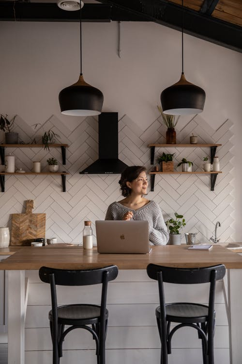 Positive young woman with laptop in cozy kitchen interior