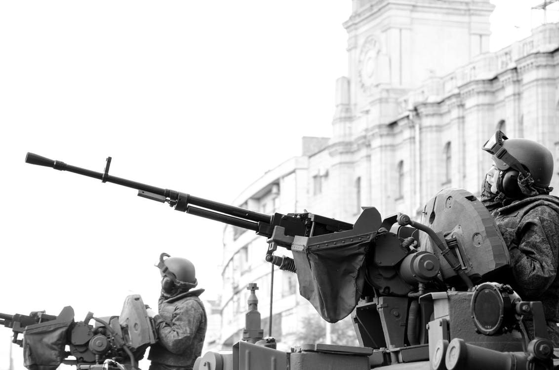 Grayscale Photo of Man Holding Rifle