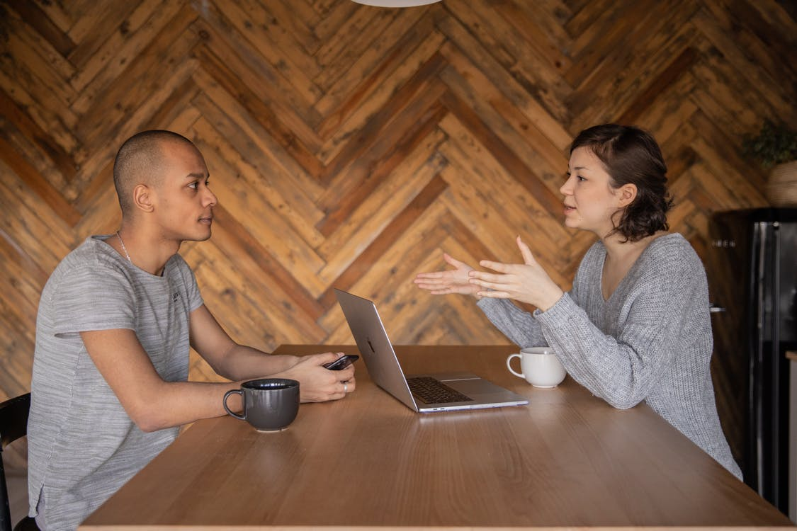 Focused woman explaining opinion to ethnic male coworker during business teamwork sitting at table with laptop and coffee cups in cozy kitchen against wooden wall and looking at each other