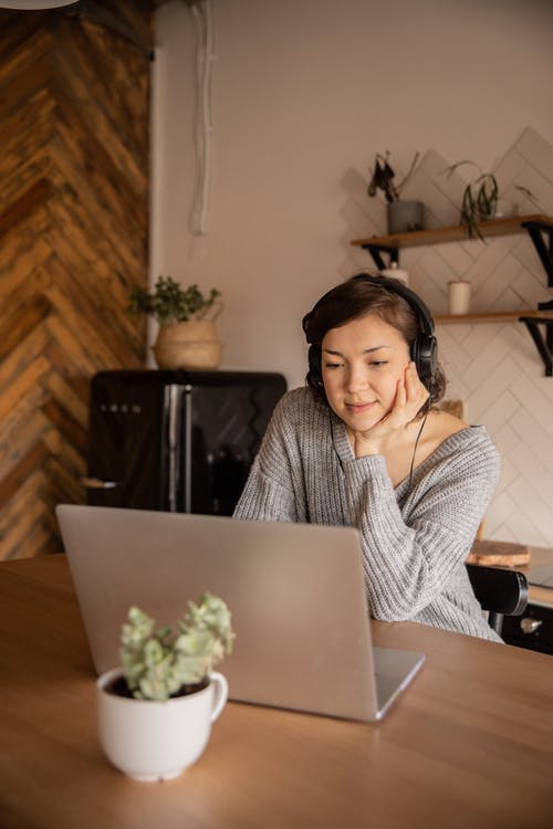 Calm female in casual clothes watching video on laptop while sitting in headphones in cozy kitchen