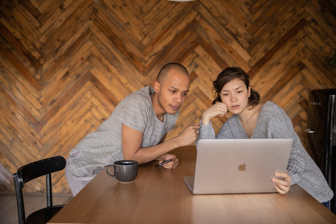 Focused couple using laptop in kitchen
