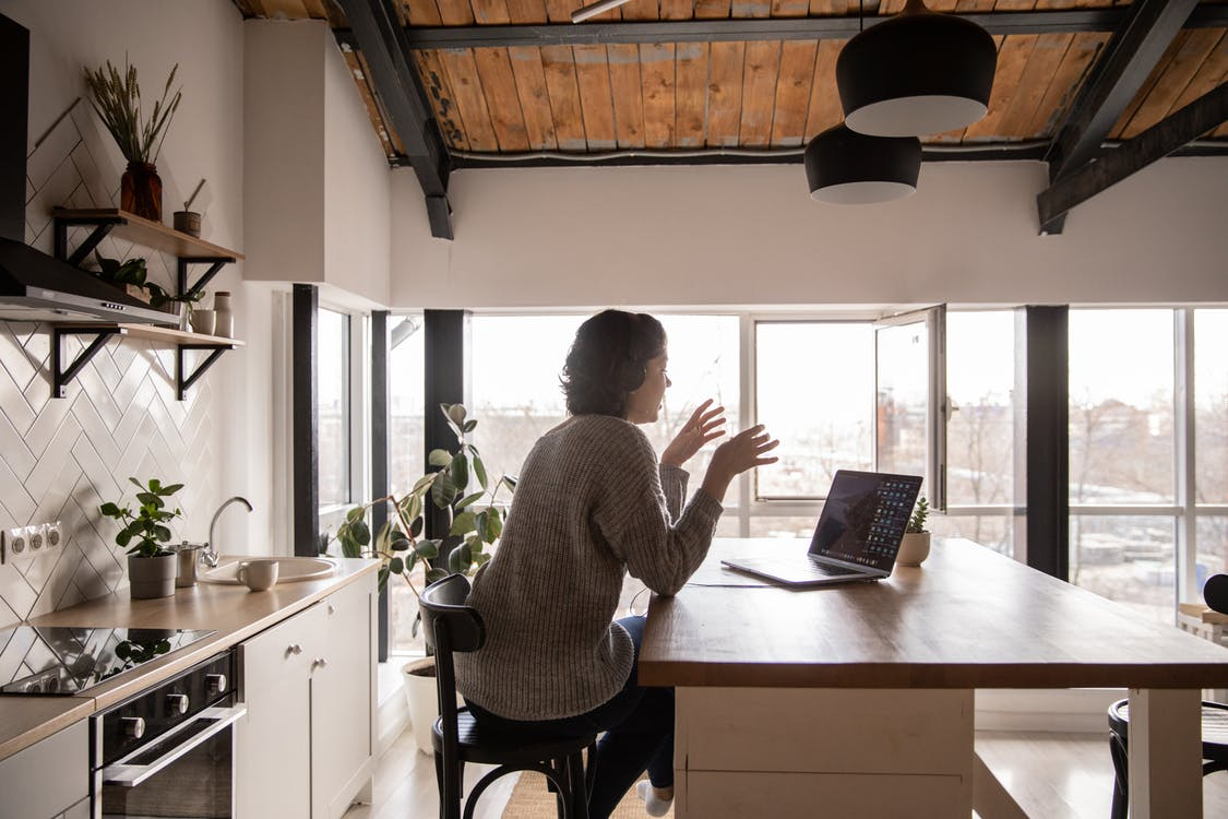 Young woman chatting via laptop in kitchen