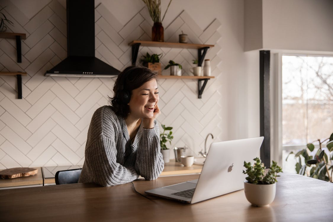 Young cheerful female smiling and talking via laptop while sitting at wooden table in cozy kitchen
