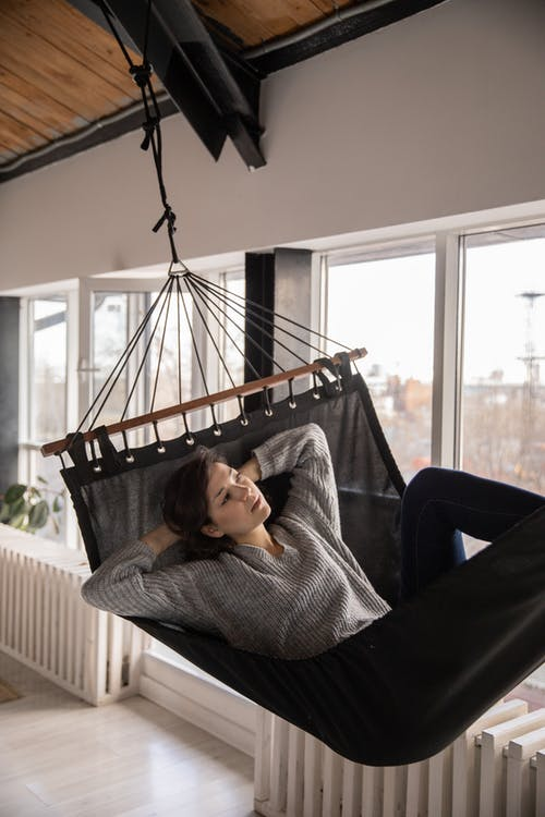 Dreamy woman laying in stylish hammock