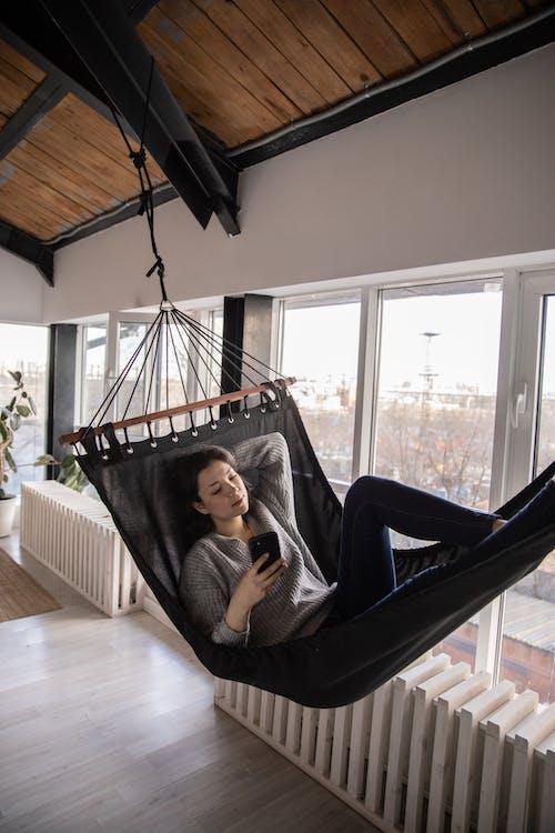 Pensive woman using smartphone while lying  in hammock