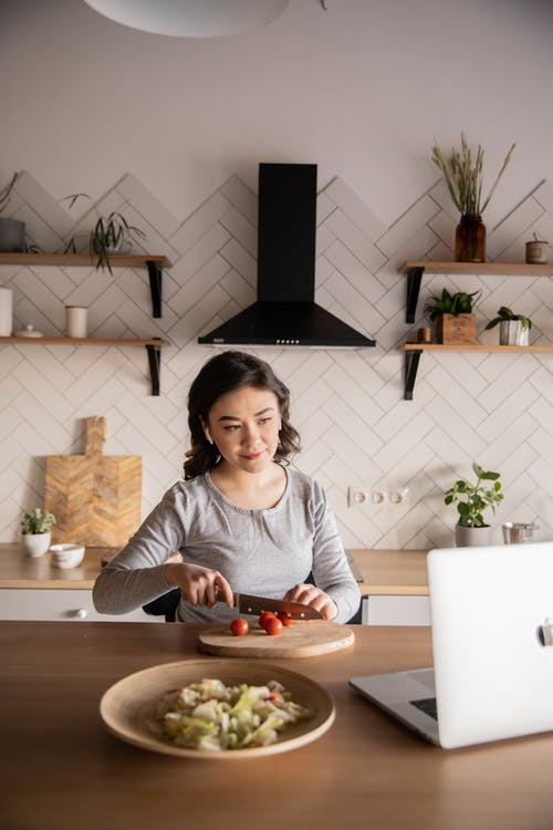 Young woman cooking while watching video on laptop