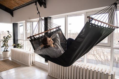 Young female in casual wear lying in comfortable hammock with eyes closed leaned on hands while sleeping in apartment near window and radiators with potted plant