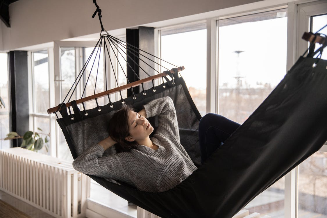 Young lady in casual wear lying in comfortable hammock leaned on hands near window and radiator in apartment in afternoon