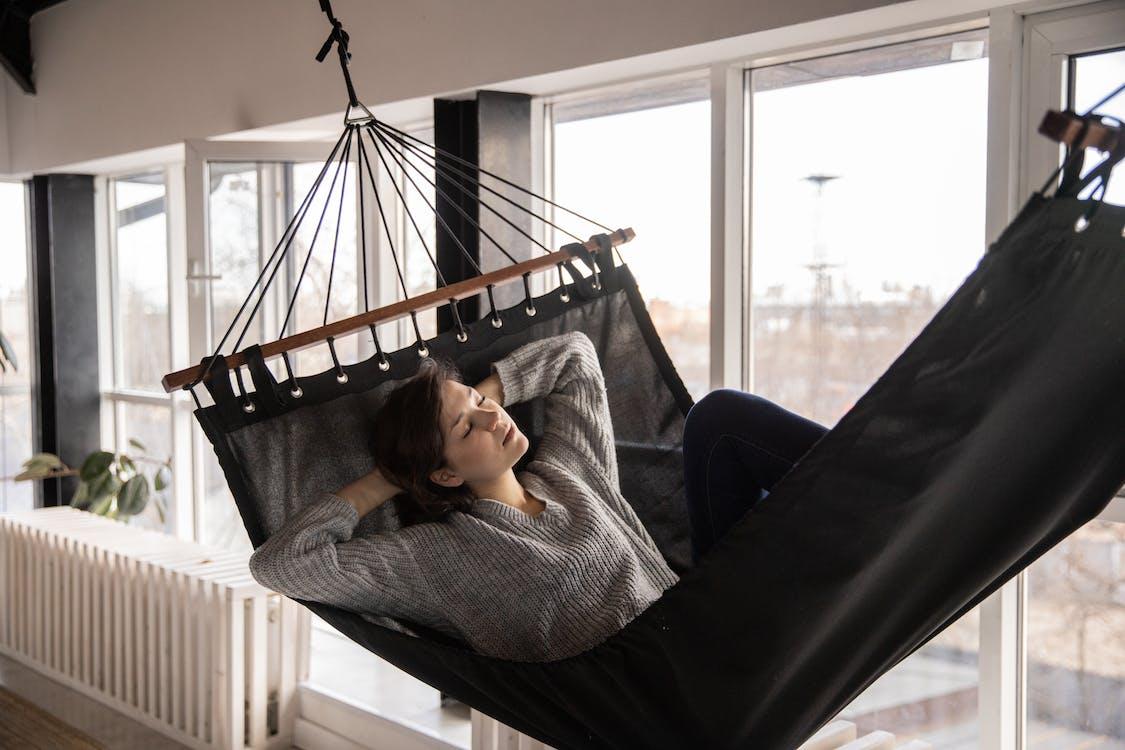 Tired woman sleeping in cozy hammock in flat