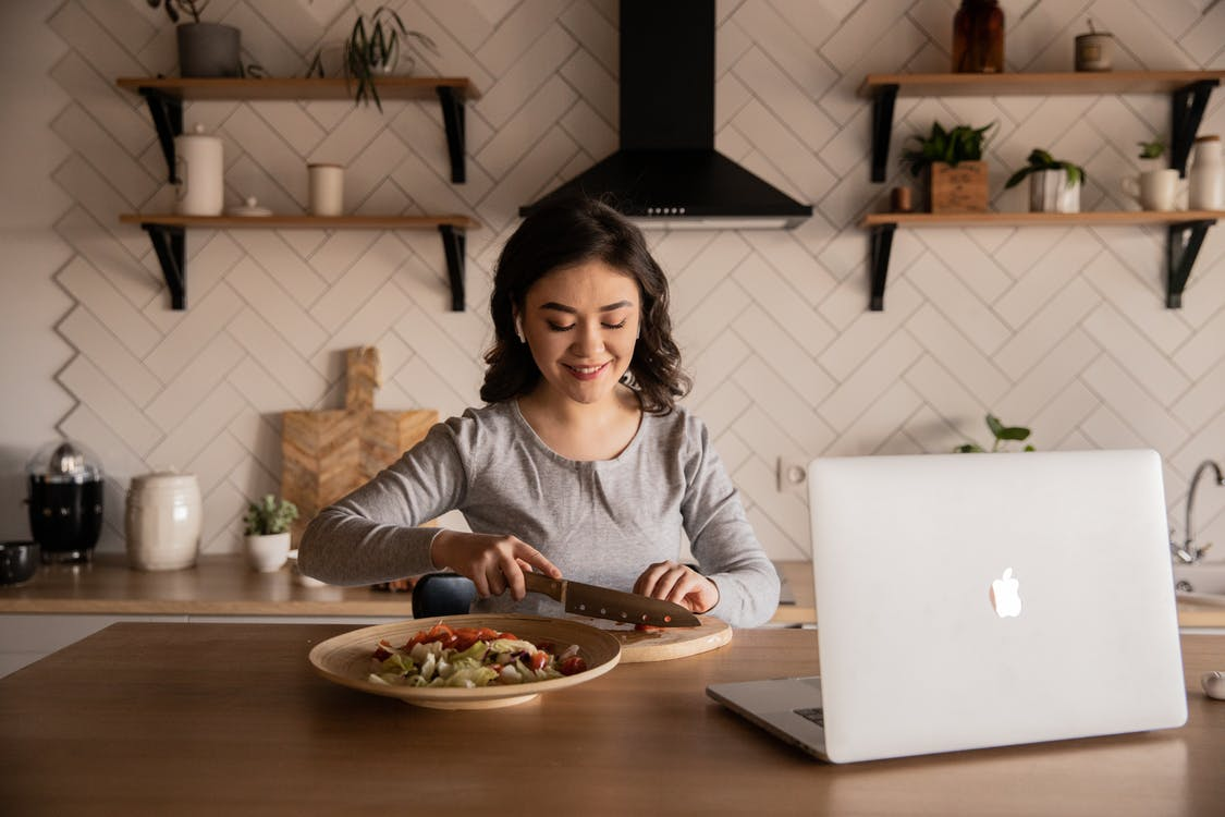 Cheerful ethnic female cutting fresh vegetables on cutting board while sitting at wooden table in kitchen with open portable computer in apartment