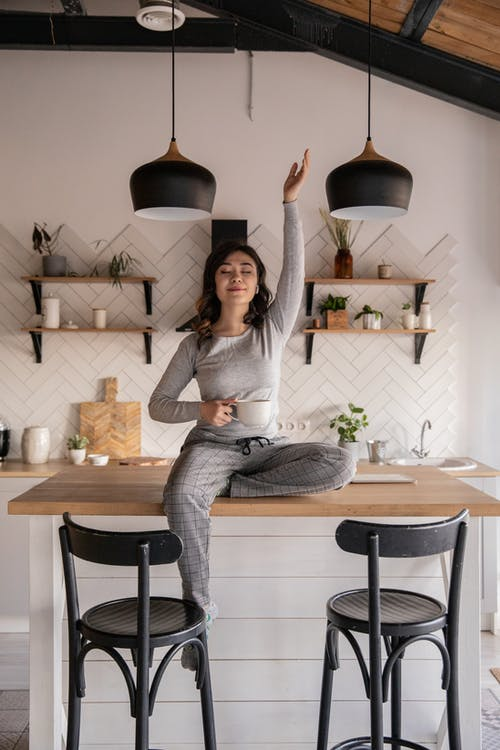 Dreamy young ethnic female with closed eyes in pajamas sitting with crossed legs on kitchen table with cup of hot drink and raised hand