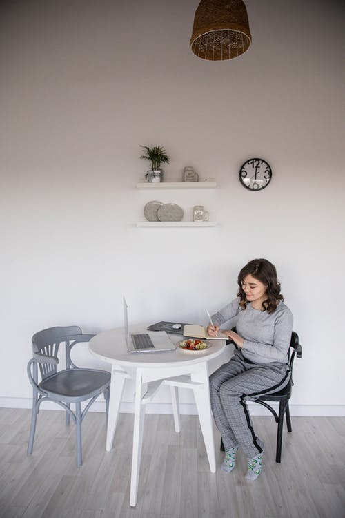 Ethnic female freelancer in casual wear writing in copybook while sitting in front of open laptop at plastic table with salad plate near white wall with clock