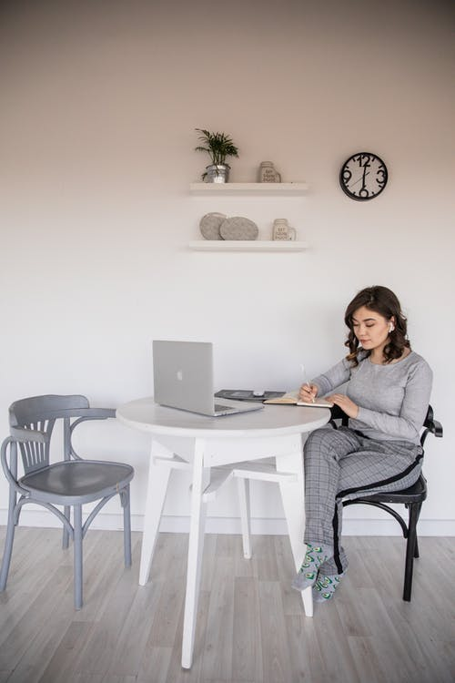 Serious young ethnic female freelancer in casual wear sitting with crossed legs at plastic table in front of open netbook while taking note in copybook in apartment
