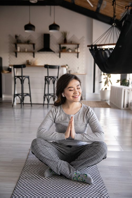 Ethnic woman sitting in Namaste pose while practicing yoga