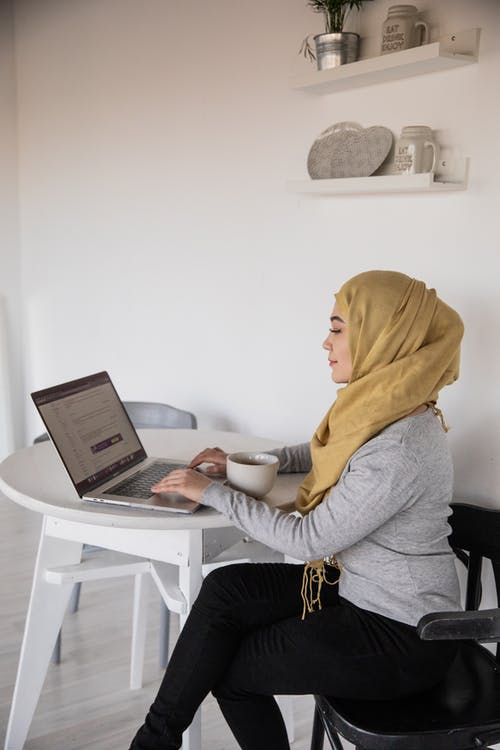 Muslim businesswoman typing on laptop during coffee break at home