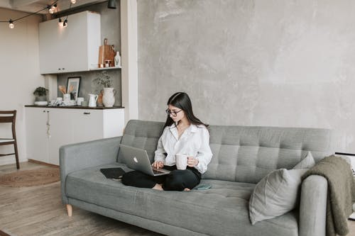 Woman Sitting On Sofa While Working At Home