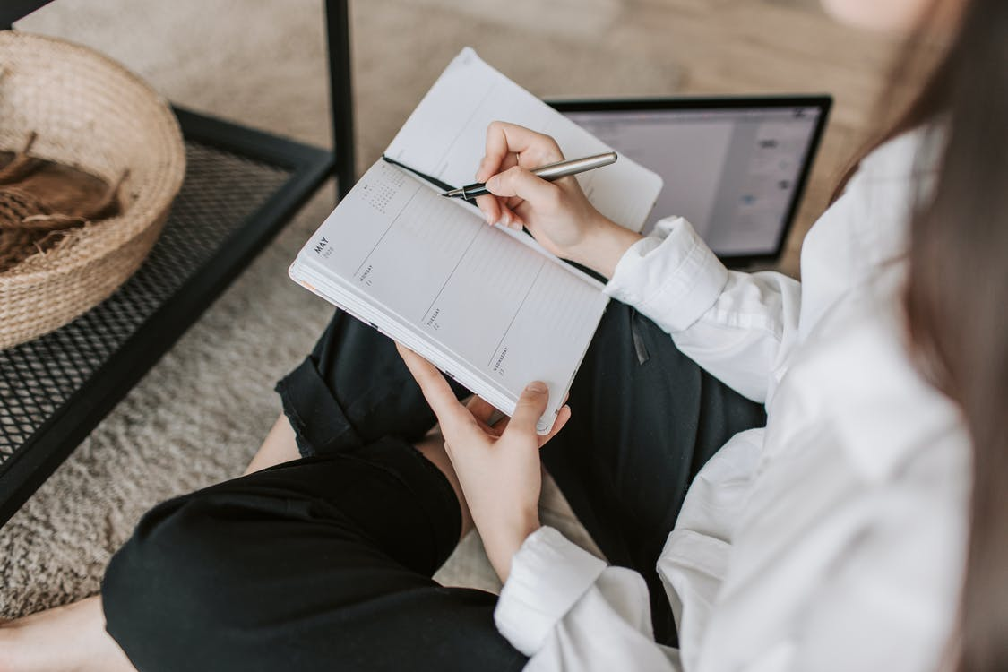 Side view of faceless woman in casual clothes taking notes on notepad while sitting in lotus pose on floor in modern apartment during daytime