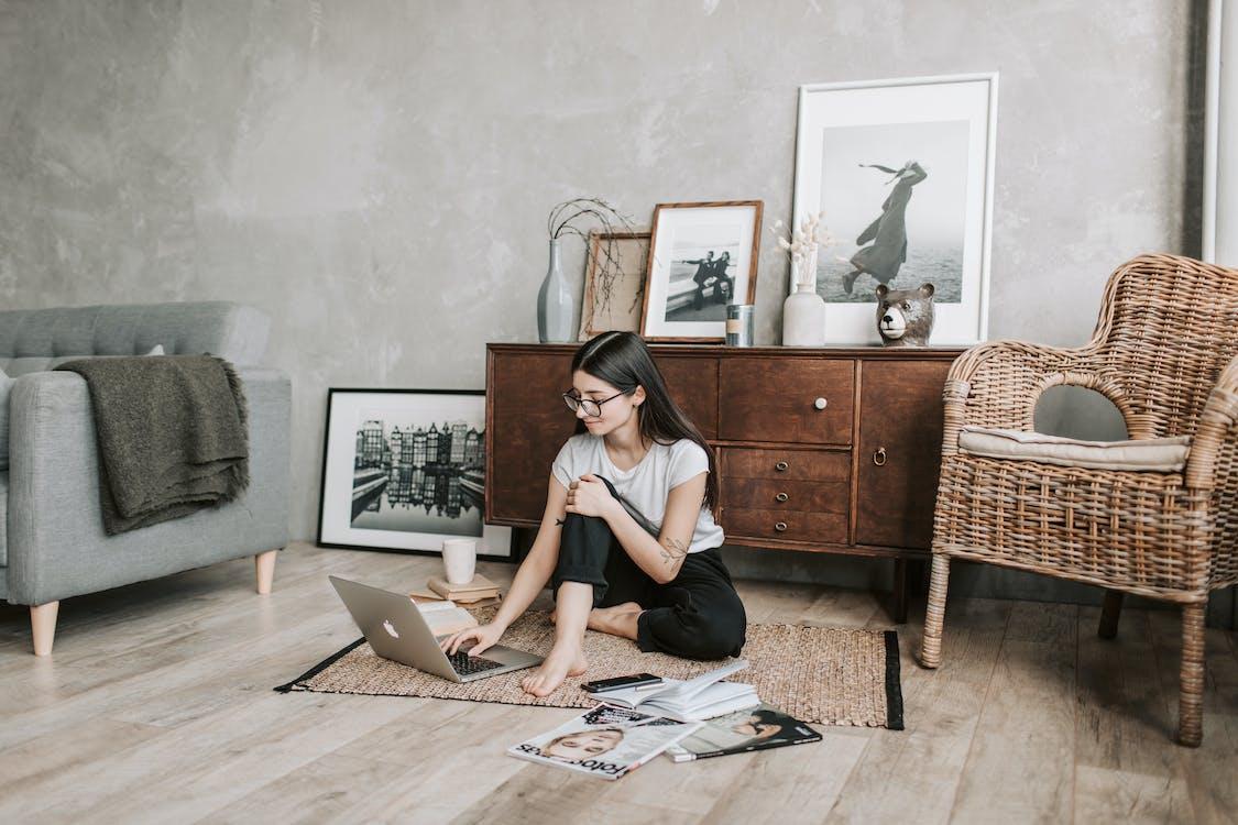 Jovem mulher sorridente usando o laptop em casa