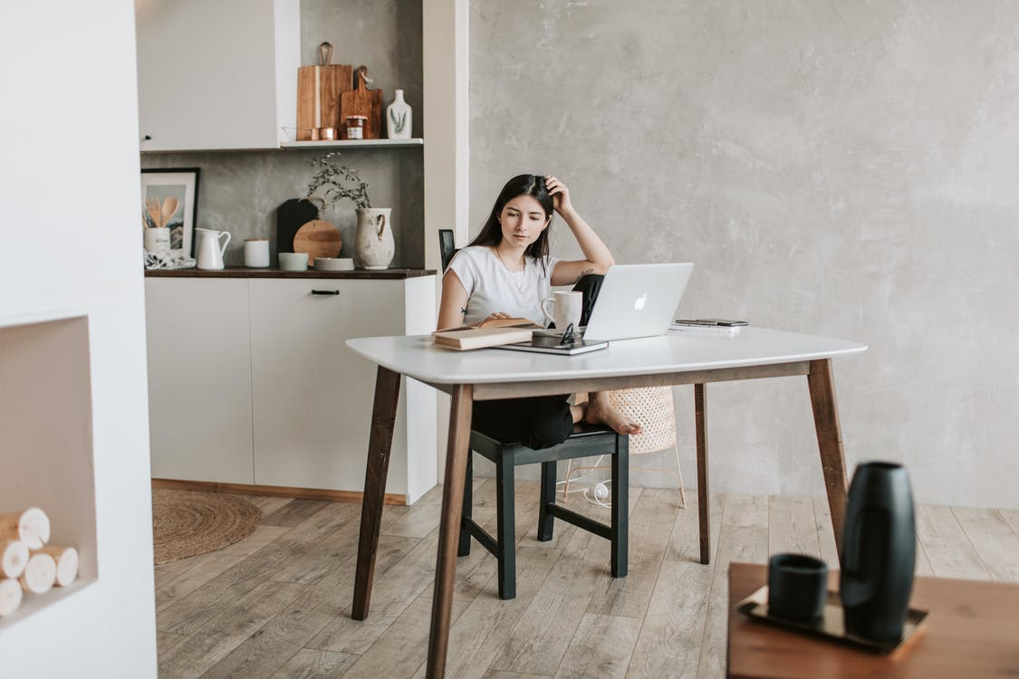 Concentrated female student sitting barefoot on chair at table with netbook and notebook while reading book during distance education in modern apartment with minimal interior in eco design