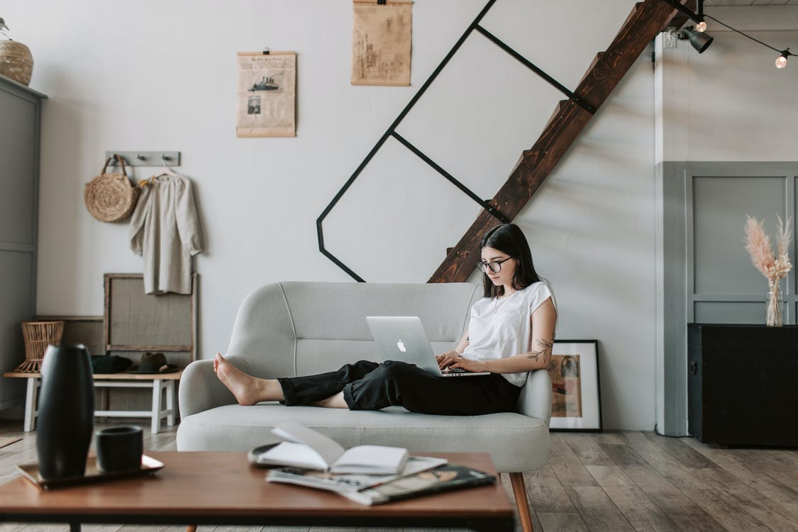 Positive female with tattooed arms wearing casual clothes and eyeglasses reading netbook while sitting barefoot on comfortable sofa behind table with books and magazines in modern apartment with minimalist interior in eco style during free time