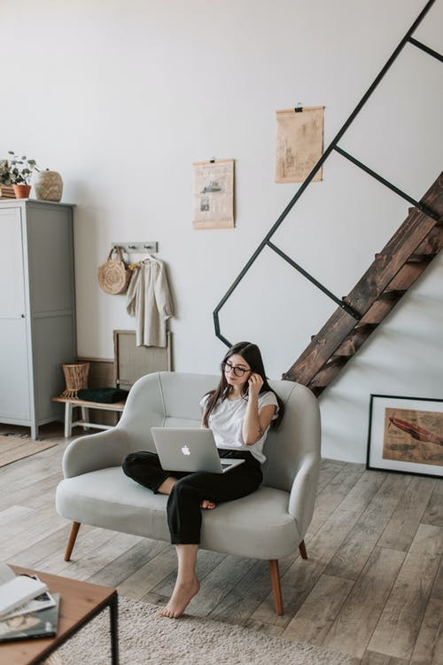 Positive young woman using laptop in modern living room with wooden staircase