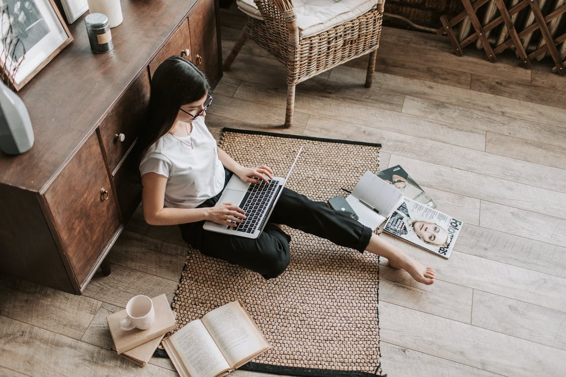 Confident young businesswoman with laptop and notebook sitting on floor modern apartment