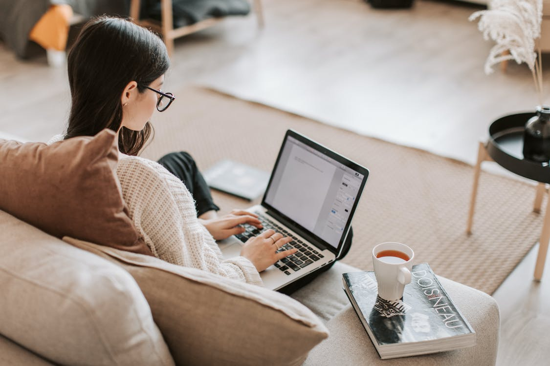 From above back view of full length female freelancer with crossed legs sitting on cozy sofa with cup of tea on book while typing text on laptop
