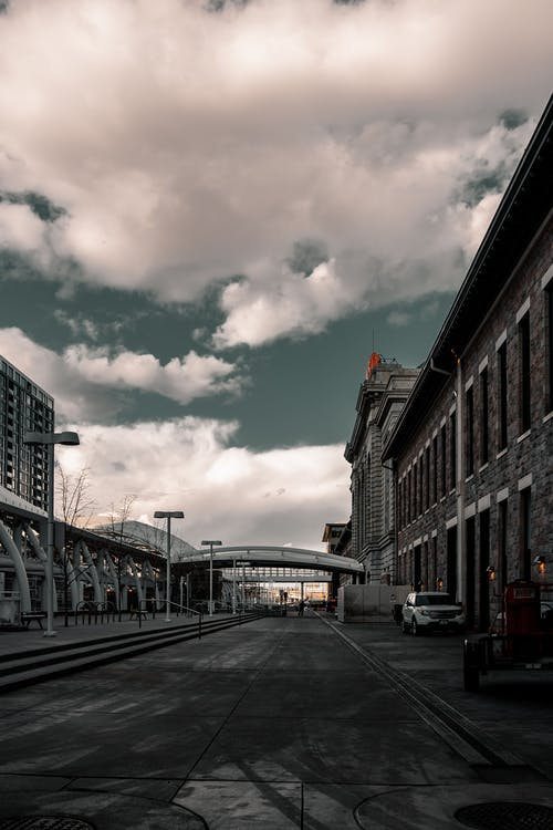 An Empty Street Under Cloudy Sky