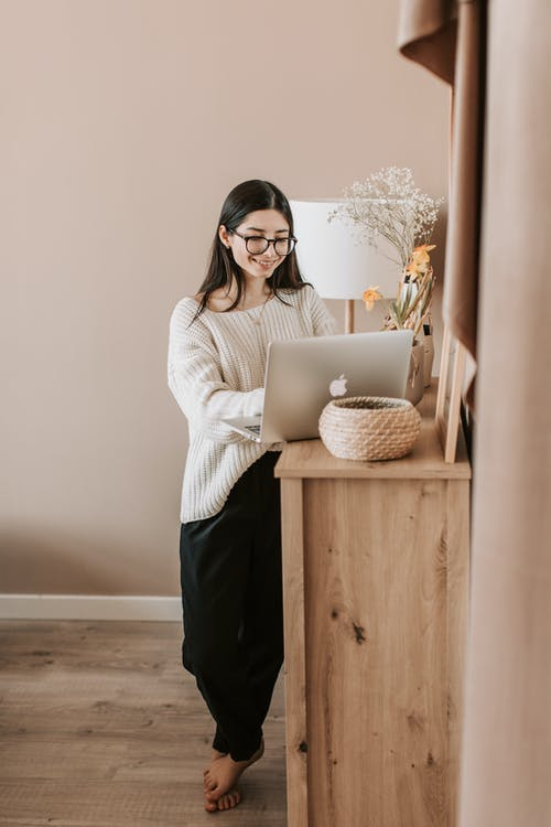 Woman Standing And Using Laptop