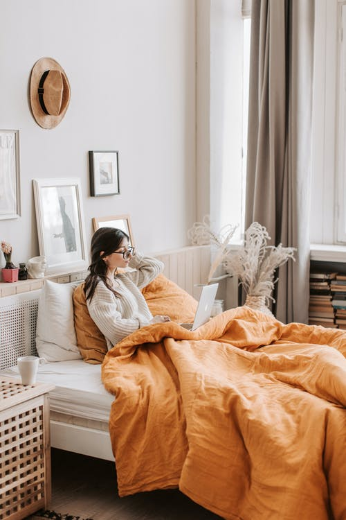 Side view of young female in warm sweater sitting on bed under blanket using laptop at cozy home apartment