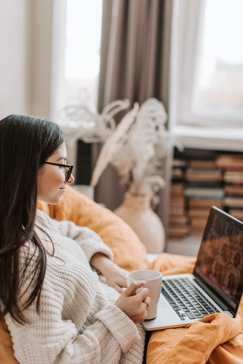 Side view of young content lady in warm white sweater and eyeglasses resting on cozy bed with mug of hot drink and browsing netbook in modern apartment in daytime