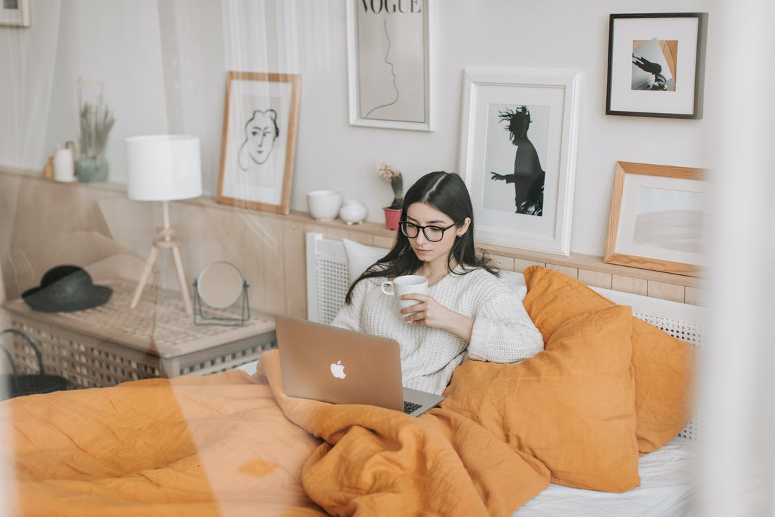 Thoughtful woman with cup of drink browsing laptop in bed