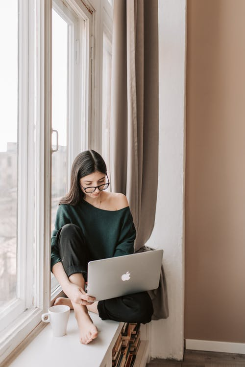 Young woman with mug using laptop on windowsill