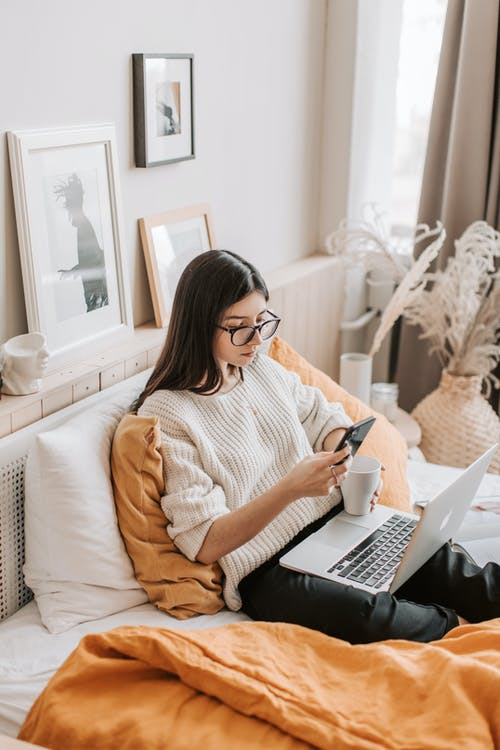 From above of thoughtful young female in warm casual clothes and eyeglasses browsing smartphone while resting on comfortable bed with laptop and cup of hot beverage in daylight
