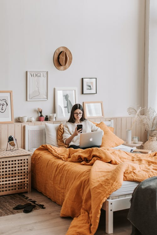 Woman with laptop and smartphone on bed