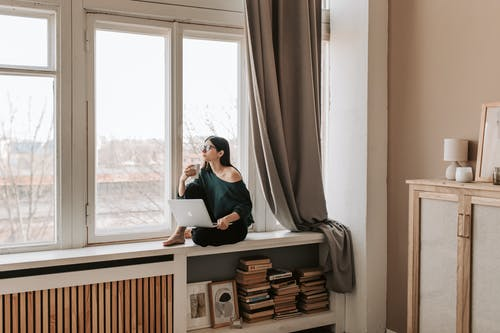 Young female in casual outfit sitting with cup of hot drink on windowsill and browsing netbook while looking out window pensively in cozy bedroom in late autumn