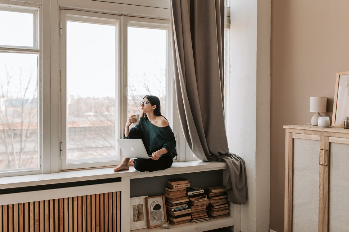 Woman with laptop and cup of drink sitting on windowsill