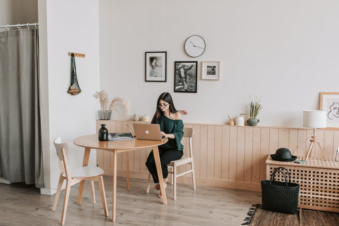 Woman working on laptop at table in modern apartment