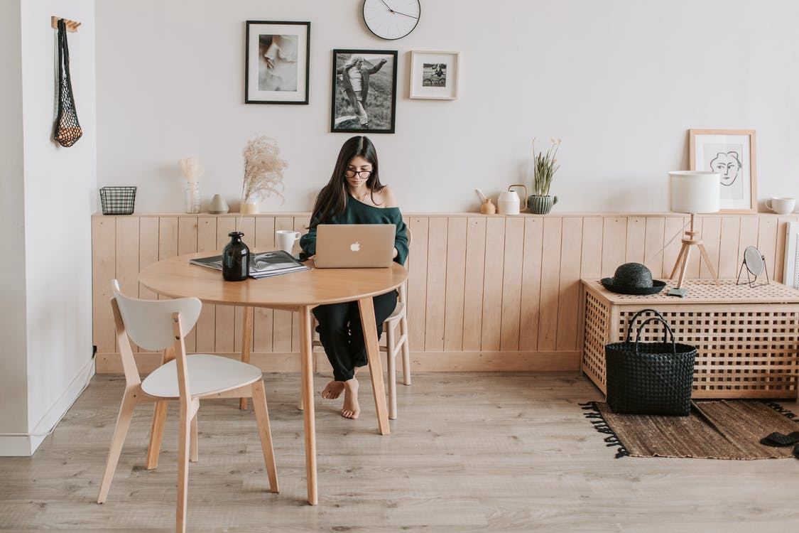 Pensive woman using laptop at home