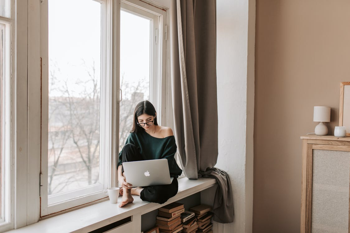 Young female freelancer sitting with laptop on windowsill at home
