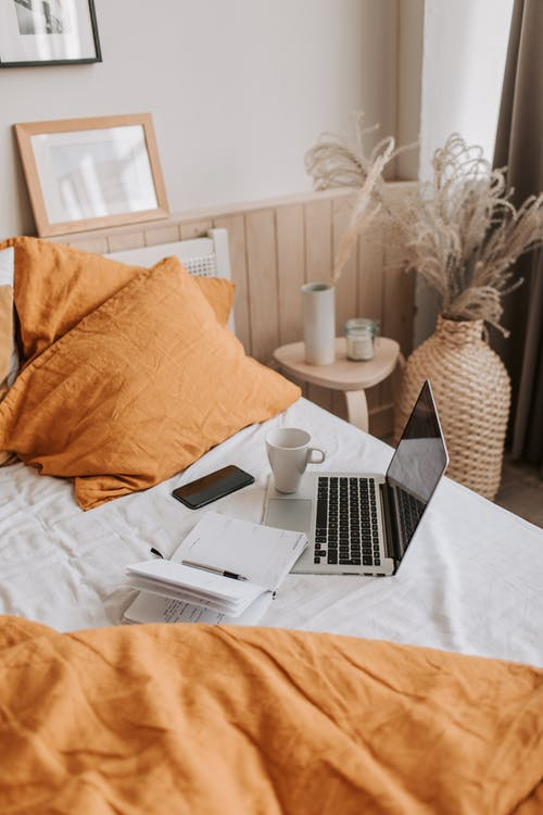 From above of open netbook with black screen and cup of coffee with smartphone and notebook placed on crumpled bed sheet in bedroom with big vase on floor