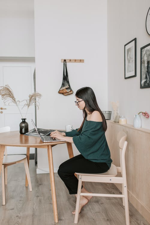 Side view of female freelancer in eyeglasses and casual wear working on netbook while sitting at wooden chair in light apartment