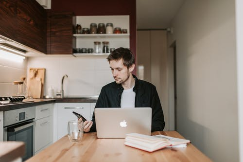 Thoughtful male freelancer using smartphone and laptop in kitchen