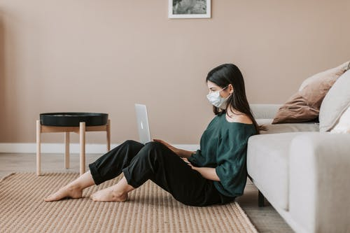 Side view of young female remote worker in casual wear and sterile mask sitting with netbook on rug leaning on sofa during COVID 19 pandemic