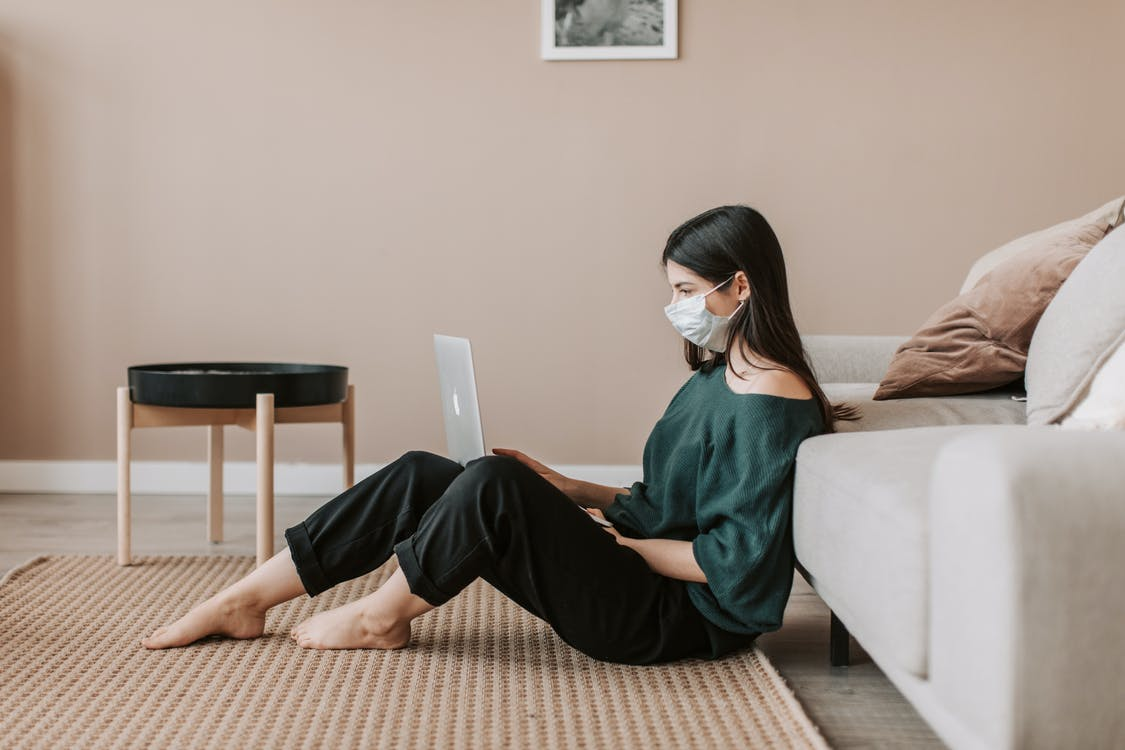 Female freelancer in face mask working on laptop at home