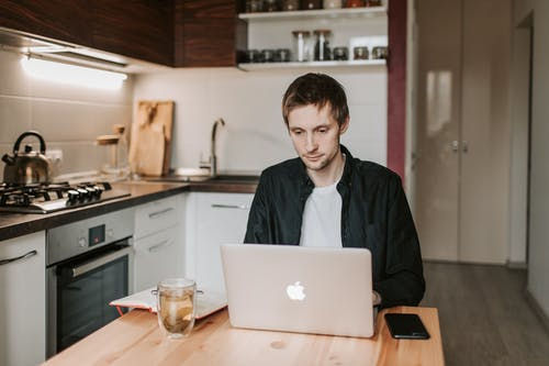 Thoughtful Man Working on Laptop in Kitchen at Home