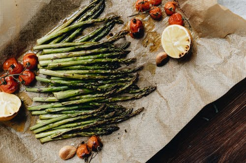 Photo Of Cooked Asparagus Near Cherry Tomatoes