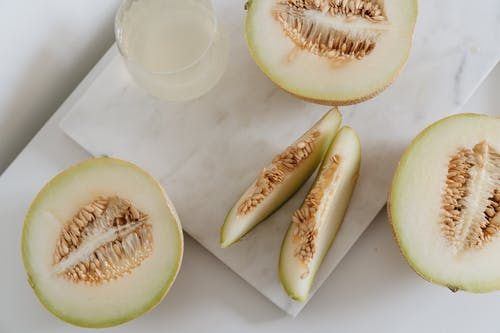 Photo Of Sliced Melon Beside Glass