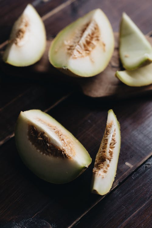 Photo Of Sliced Melon On Wooden Surface
