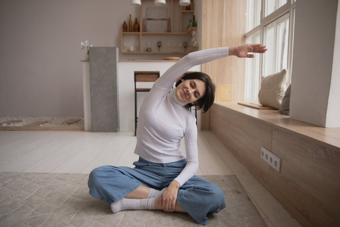 Smiling woman practicing yoga with closed eyes at home